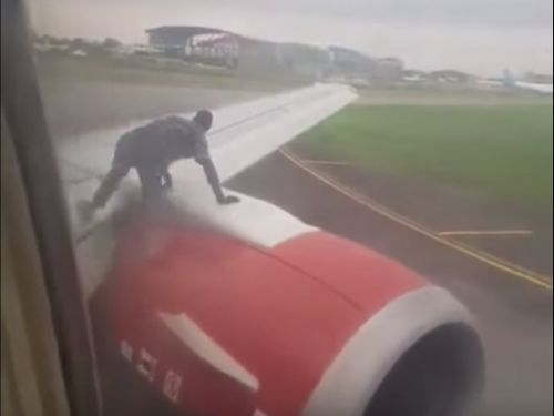 A flight was delayed when a man tried climbing onto the airplane's wing to hitch a free ride