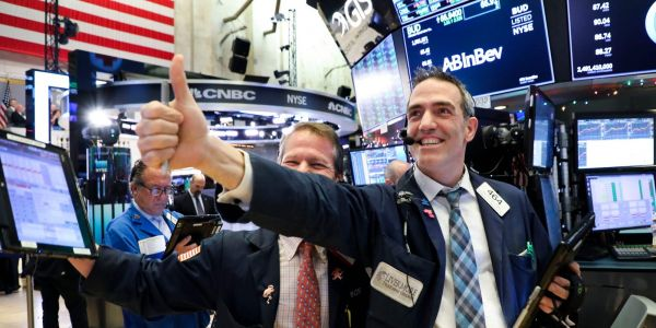 Dow closes at record high as Powell signals Fed to remain accommodative