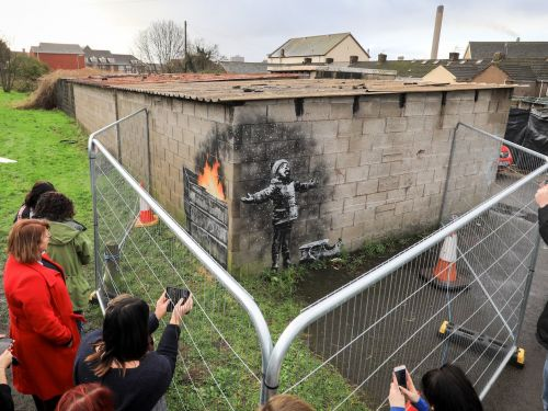 A Banksy artwork found on the side of a garage in Wales has been sold for six figures