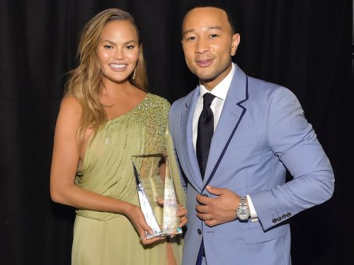 Chrissy Teigen hilariously removed 2 of John Legend's Grammys off a shelf to make room for her Baby2Baby award