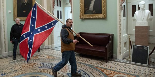 A man accused of storming the Capitol with a giant Confederate flag will get to go on a family vacation while awaiting trial